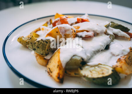Kizartma, Turkish kitchen food, fried vegetables with yoghurt.Fried eggplant, squash, potatoes, tomatoes with spices and yoghurt served on a plate. - Stock Photo