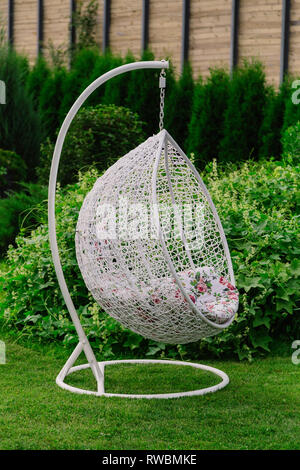 Suspended white cocoon chair on green grass. - Stock Photo