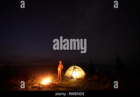 Night camping in mountains. Young tourist girl standing near illuminated tent and burning campfire on deep dark sky with lot of bright sparkling stars background. Tourism and outdoor activity concept. - Stock Photo