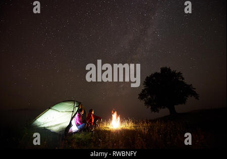 Tourist couple man and woman having a rest near illuminated tent, burning campfire and silhouette of big tree under starry sky, enjoying night camping in mountains. Tourism, outdoor activity concept - Stock Photo