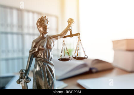 Lady Justice statue in law firm attorney office, blindfolded Justitia with balance scales and sword is personification of moral force in judicial syst - Stock Photo