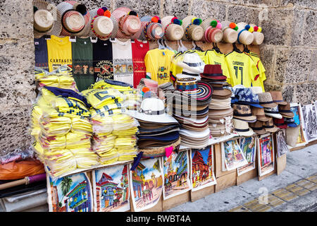 Cartagena Colombia Old Walled City Center centre Centro shopping display sale souvenir sidewalk vendor traditional straw hats t-shirts - Stock Photo