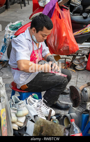 Man working as a cobbler , repairing shoes, on the pavement in the Old Quarter of Hanoi, Vietnam, Asia - Stock Photo