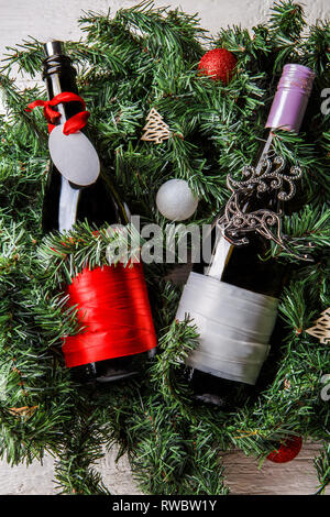 Photo of two Christmas bottles with clean greeting card on spruce branches - Stock Photo