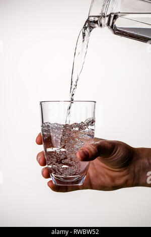 Man pours water from pitcher - Stock Photo