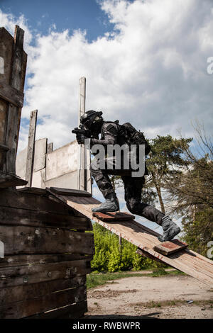 Spec ops police officer SWAT in black uniform in action. - Stock Photo