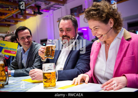 06 March 2019, Bavaria, Dingolfing: Nicola Beer (r-l), top candidate of the FDP in the European elections, Daniel Föst, FDP Member of Parliament and Martin Hagen, chairman of the FDP parliamentary group, have a beer at the Political Ash Wednesday of the FDP. Photo: Sina Schuldt/dpa - Stock Photo