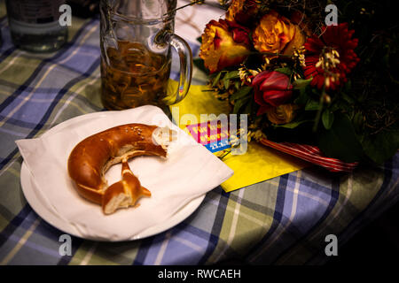 06 March 2019, Bavaria, Dingolfing: After the Political Ash Wednesday meeting of the FDP, a half eaten pretzel is lying on a plate. Photo: Sina Schuldt/dpa - Stock Photo
