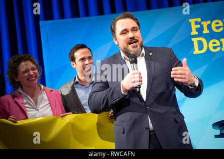 06 March 2019, Bavaria, Dingolfing: Daniel Föst (r), FDP Member of Parliament, speaks at the FDP Political Ash Wednesday. In the background are Nicola Beer (l), leading candidate of the FDP in the European elections and Martin Hagen (r), chairman of the FDP parliamentary group. Photo: Sina Schuldt/dpa - Stock Photo