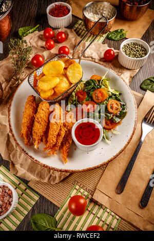 Shrimps tempura with spicy chili sauce, fresh salad and fried potatoes. Pub food - Stock Photo