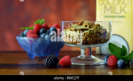 Grain free oat free paleo diet granola breakfast served with fresh seasonal berries, coconut milk, and coconut yoghurt. - Stock Photo