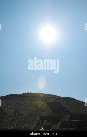 Sunshine and tourists on top of Pyramid of the Sun at Teotihuacan, Mexico - Stock Photo