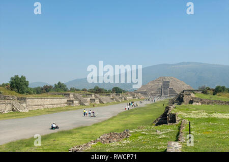 Tourists walking on Avenue of the Dead and the view of Pyramid of the Moon at Teotihuacan, Mexico - Stock Photo