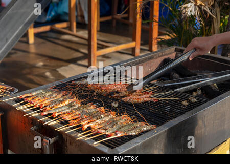 Hand holding a kitchen tong for turning prawns on a coal-fired grill, picture from Phu Quoc Island, Vietnam. - Stock Photo