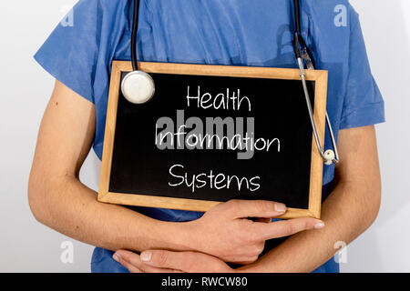 Doctor shows information on blackboard: health information systems.  Medical concept. - Stock Photo
