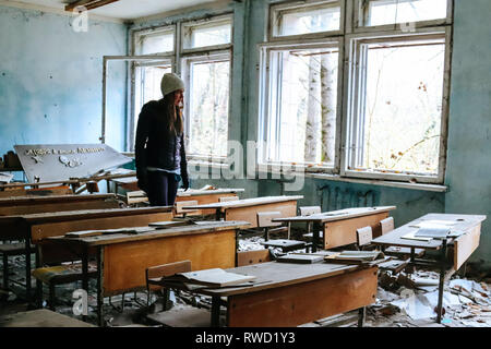 Woman walks through a classroom that was abandoned long ago in wake of the Chernobyl nuclear disaster - Stock Photo