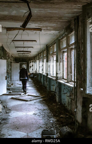 Woman walks through abandoned hallways of a school inside Chernobyl's Exclusion Zone - Stock Photo