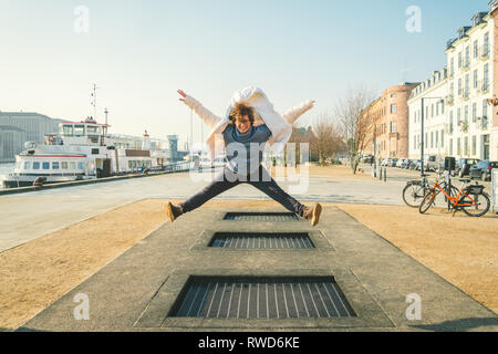 adult person rejoices like child. Playground trampoline in ground, children trampoline, springs throws people up fun and cool. Copenhagen River Embank Stock Photo