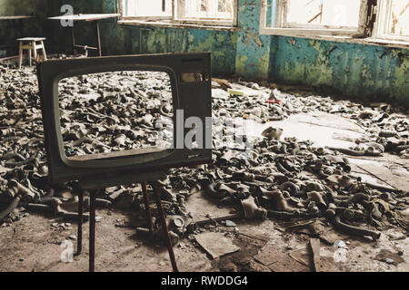 Gas masks that were aquired in case of chemical attack during the cold war now lay on the floor of a classroom inside the Chernobyl exclusion zone. - Stock Photo