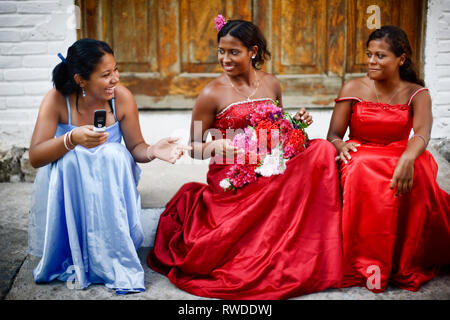 Girls in prom dresses sitting and laughing, El Salvador. - Stock Photo