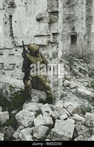 Post apocalypse survivor in tatters and gas mask on the ruins of a destroyed city. - Stock Photo