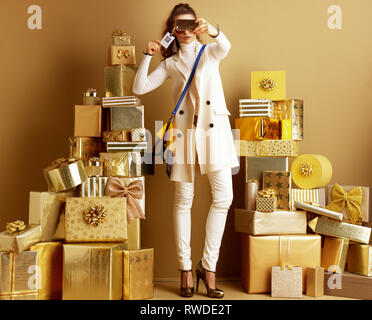 Full length portrait of glam young fashion-monger taking selfie with smartphone while wearing sunglasses with price tag with qr code among 2 piles of  - Stock Photo