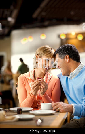Affectionate mature couple enjoy eating breakfast together at a cafe. - Stock Photo