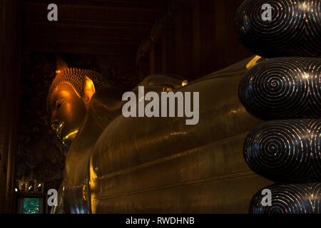 Gold plated body and toes of reclining Buddha statue in Wat Pho temple, Bangkok, Thailand