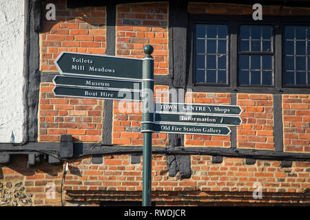 Tourist information and direction sign in Henley-on-Thames, Oxfordshire in front of medieval house with exposed timbers. - Stock Photo