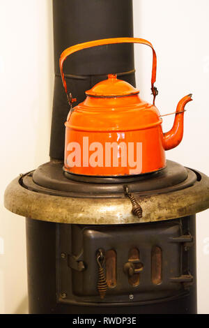 Old stove with orange kettle. - Stock Photo