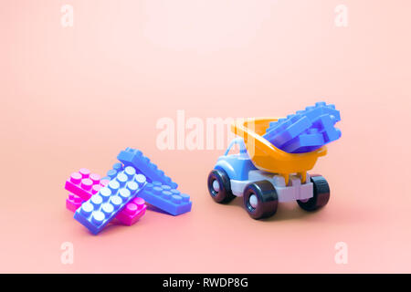 Truck toy model car with blocks of constructor on pink background - Stock Photo