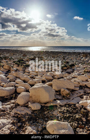 Calm beach full of white rocks on a sunny day with blue sky and clouds - Stock Photo