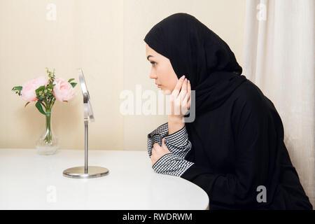 Attractive young woman wearing hijab at home. Beautiful Muslim girl wearing hijab. - Stock Photo