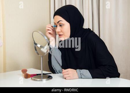 Beautiful muslim woman applying mascara. Young arab woman using lash brush - Stock Photo