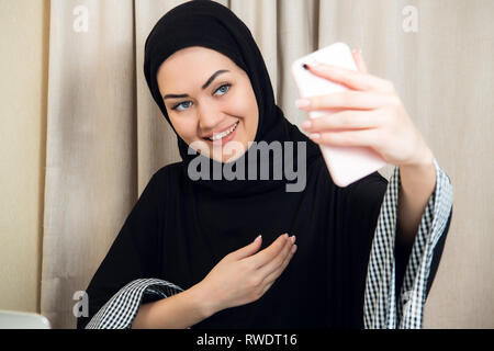 Beautiful young arabic woman taking selfie with her mobile phone - Stock Photo