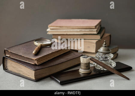 Several of antic books, set of old stationery, wooden pen, inkwell, magnifier close-up, vintage background. Concept of reading and education, memory - Stock Photo