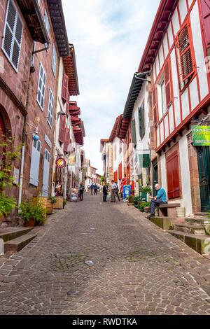SAINT-JEAN-PIED-DE-PORT, FRANCE - MAY 04, 2017: Pilgrims in Rue de la Citadelle, Citadelle Street in Saint-Jean-Pied-de-Port, Basque Country, France - Stock Photo
