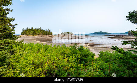Framed view on islands and inlet at low tide on a sunny afternoon on the St. Lawrence River, Parc National du Bic, Province of Quebec, Canada - Stock Photo