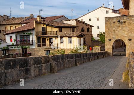 Puente la Reina urban skyline with the Romanesque bridge across Arga River and a bridge gate, in Navarre Spain - Stock Photo