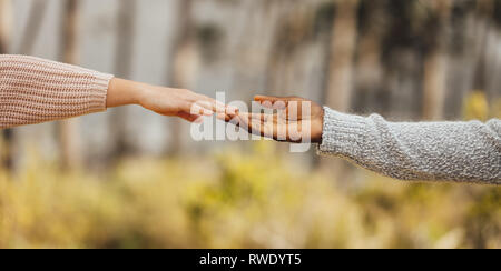 Multi-ethnic couple hands reaching and touching outdoors. Couple approaching to each other. Female and male hands touching each other by fingers. - Stock Photo