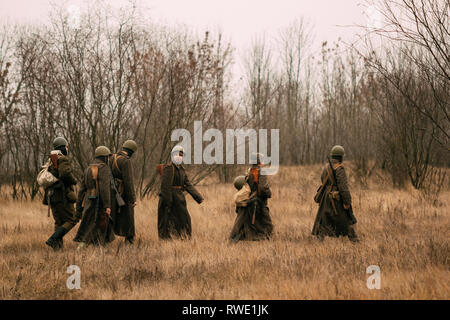 Gomel, Belarus - November 26, 2017: Soldiers of the Red Army in uniform go to positions on the autumn field. Reconstruction of the liberation of the city of Gomel - Stock Photo