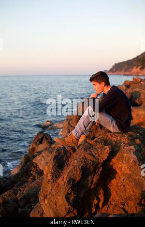 Handsome boy looking out to sea at sunset, Lluc Alcari, Deia, Mallorca Spain - Stock Photo