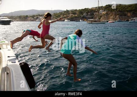 Kids jump from boat into mediterranean sea - Stock Photo