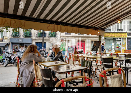 Two woman talking and enjoying a pot of tea at a restaurant in St Georges in the 9th arrondissement of Paris - Stock Photo