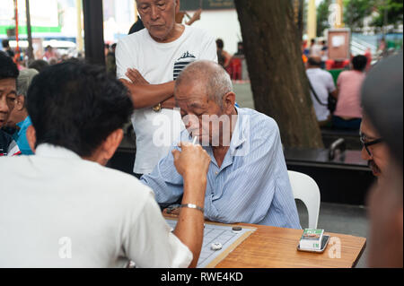 24.02.2019, Singapore, Republic of Singapore, Asia - Men are playing Chinese chess next to the Buddha Tooth Relic Temple in Chinatown. - Stock Photo