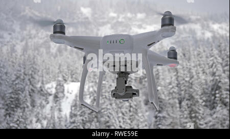 A drone hovers in flight in front of the Camera against a snow white forest alpine background. The drone is close up in the foreground. - Stock Photo