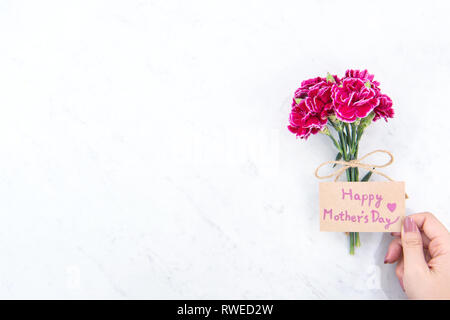 May mothers day idea concept photography - Beautiful blooming carnations tied by rope kraft bow holding in woman's hand isolated on bright modern tabl - Stock Photo