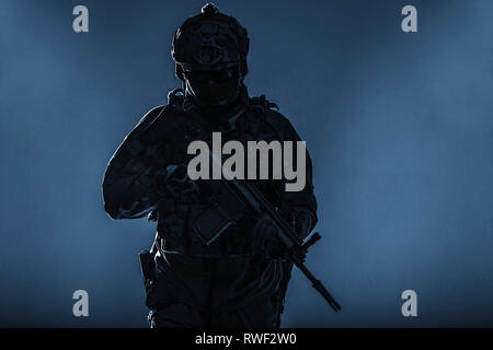 Silhouette of an Army soldier in Protective Combat Uniform holding assault rifle. - Stock Photo