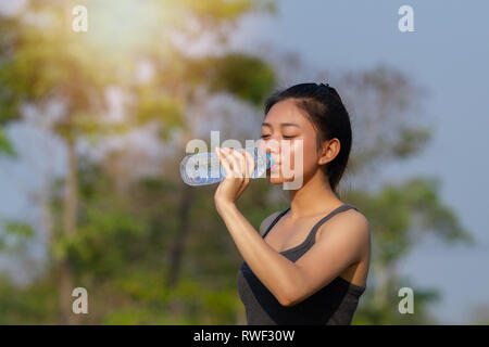 Sporty woman asian drinking water outdoor on sunny day - Stock Photo