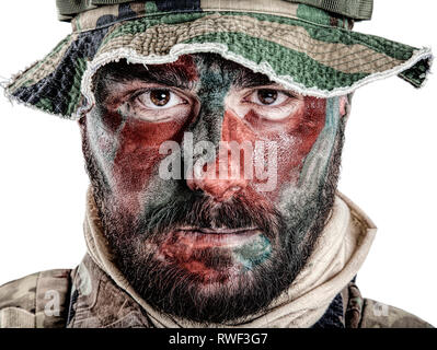 U.S. special forces soldier wearing jungle hat with painted red and green face. - Stock Photo